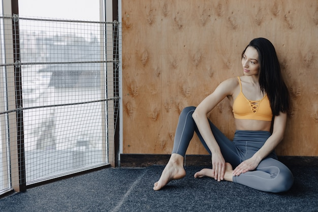 Young attractive fitness girl sitting on the floor near the window on the background of a wooden wall, resting on yoga classes