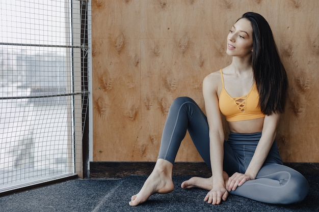 Young attractive fitness girl sitting on the floor near the window on the surface of a wooden wall, resting on yoga classes