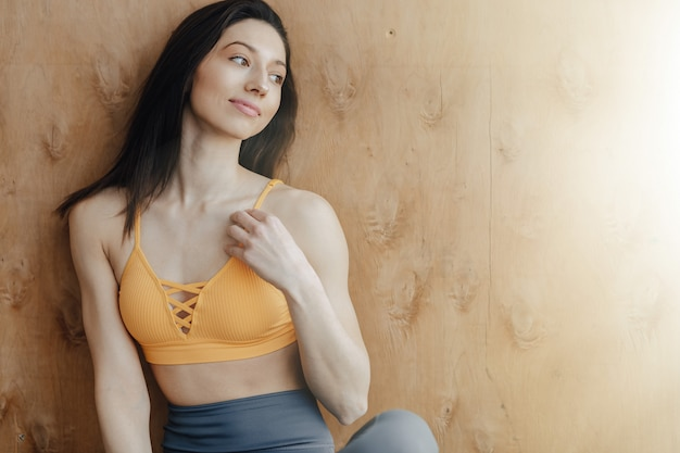 Young attractive fitness girl sitting on the floor near the window on the wall of a wooden wall, resting on yoga classes