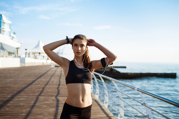 Young attractive fitness girl with sea coast on wall