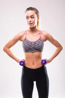 La giovane donna attraente della ragazza di forma fisica fa gli esercizi differenti di aerobica con i dumbbells su bianco