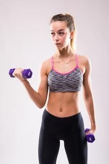 La giovane donna attraente della ragazza di forma fisica fa gli esercizi di aerobica muscolare diversi con i dumbbells su bianco vestito in abiti sportivi