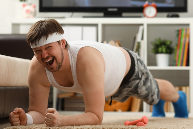 Young attractive fitness man lies on a fat mat with