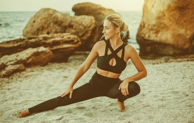 야생 해변에서 훈련하기 전에 모래 위에서 다리를 쭉 뻗고 있는 운동복을 입은 젊고 매력적인 여성. 스포츠 훈련. 야외에서 운동