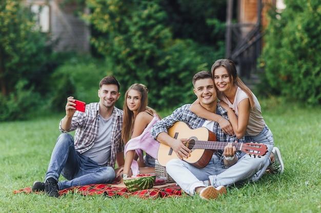 젊고 매력적인 4명이 공원의 담요 카펫에 앉아 휴식을 취하고 있다