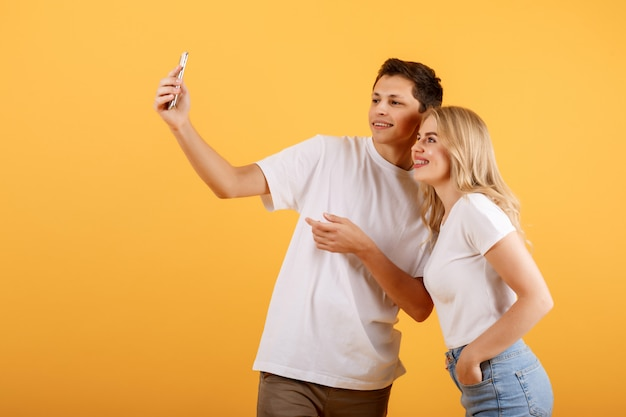 Young, attractive friends on an orange background taking selfies