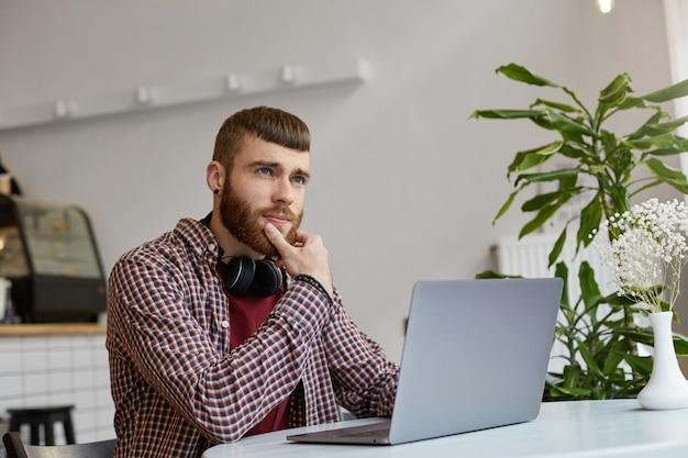 Молодой привлекательный рыжий бородатый мужчина сидит за столиком в кафе и работает за ноутбуком, одет в простую одежду, задумчиво смотрит в сторону, пытаясь придумать решение.