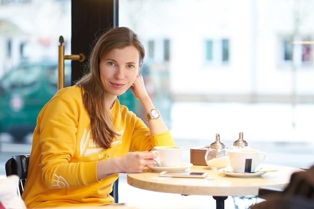 Молодая привлекательная рыжая кавказская девушка в желтом свитере пьет кофе в кафе и улыбается