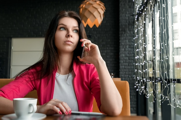 Young attractive girl, businesswoman, talking on mobile phone sitting alone in coffee shop