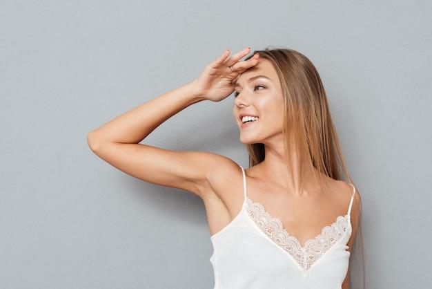 Молодая привлекательная девушка закрыла глаза рукой, изолированной на сером фоне