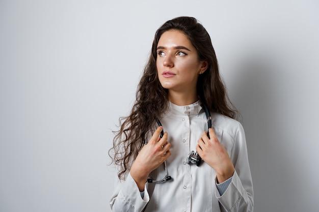 Молодая привлекательная девушка-врач в медицинском халате. молодая женщина уверенно на белом фоне. реклама медицинской клиники и блоги.