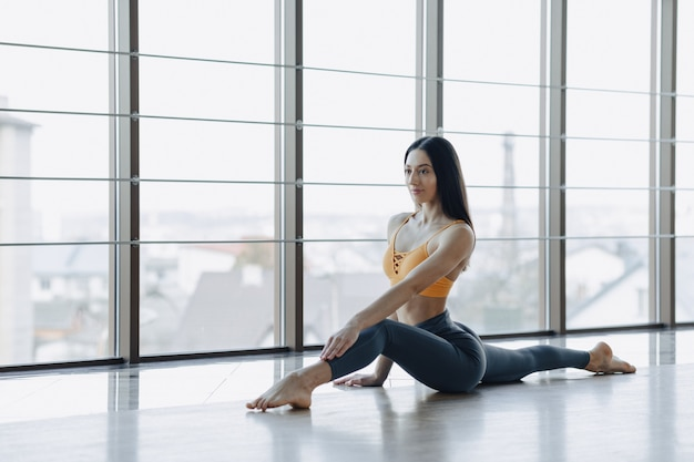 Young attractive girl doing fitness exercises with yoga on the floor against the surface of panoramic windows