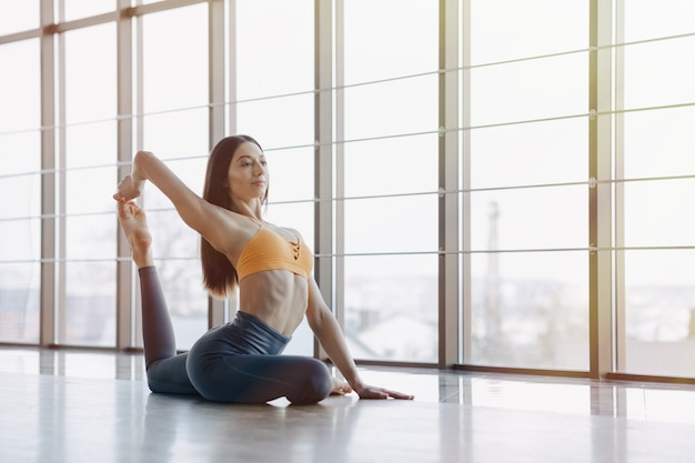 Young attractive girl doing fitness exercises with yoga on the floor