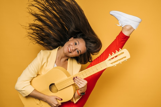 Молодая привлекательная девушка в желтой куртке и красных штанах держит желтую гитару, танцует с развевающимися длинными волосами и высоко поднимает ногу