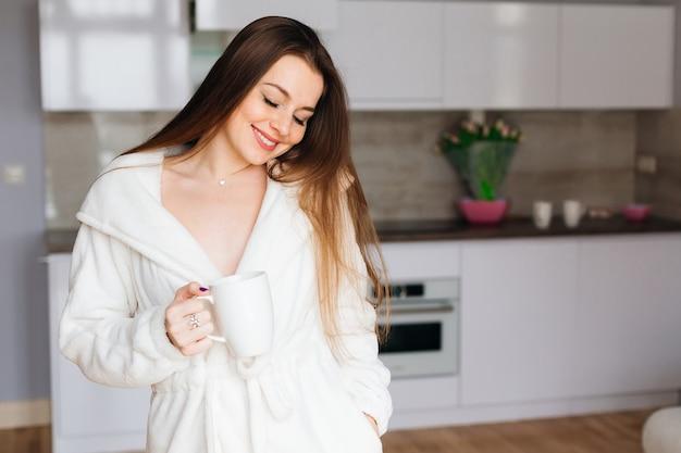 大きな白いカップから朝のコーヒーを飲む、笑顔、朝の肖像画の若い魅力的な女の子。スペースをコピーします。