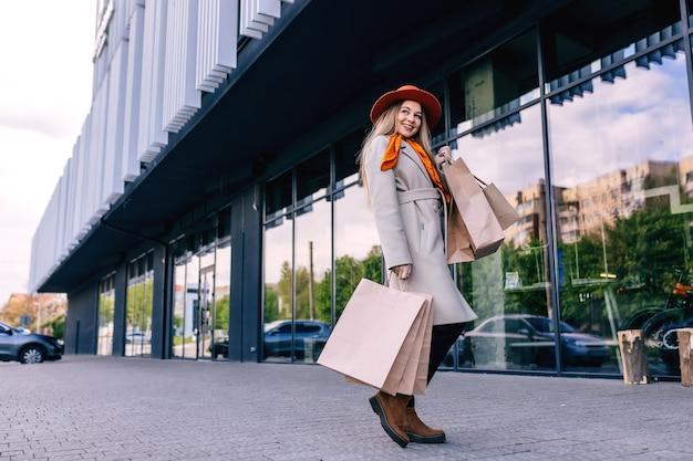 手にバッグを持って、街で良い買い物を楽しんでいる若い魅力的な女の子