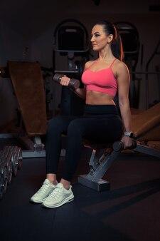 ジムでダンベルで運動する若い魅力的な女の子