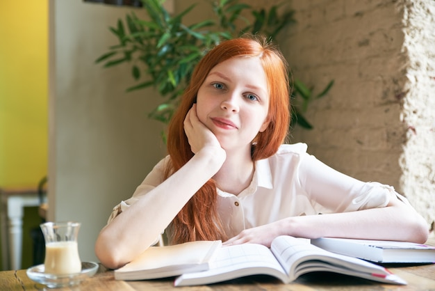 하얀 피부와 긴 붉은 머리를 가진 젊은 매력적인 여자 여자 학생 책을 읽고, 공부, 카페 테이블에 책으로 둘러싸인 자연 채광에 초상화에 대 한 포즈