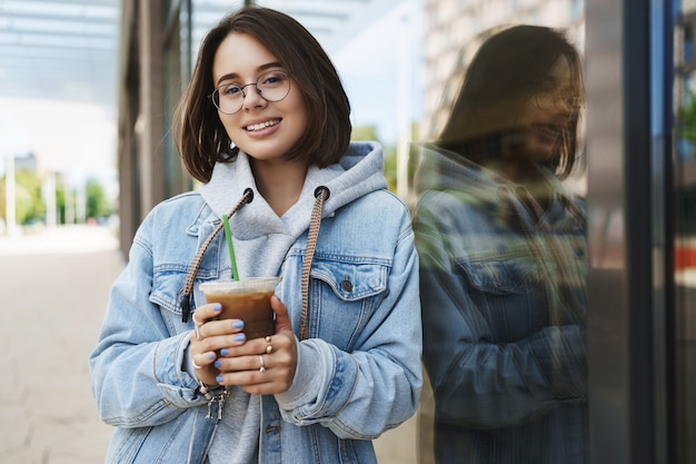Young attractive girl in glasses, denim jacket, having casual walk in city, enjoying weekends, drinking ice latte, leaning on building wall and smiling camera with happy relaxed expression.