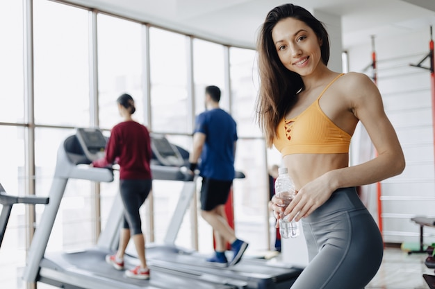 Young attractive girl in the gym drinking water on the background of treadmills