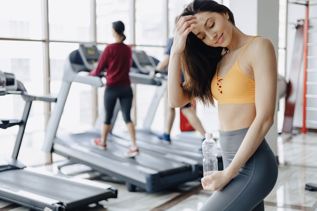 Young attractive girl in the gym drinking water