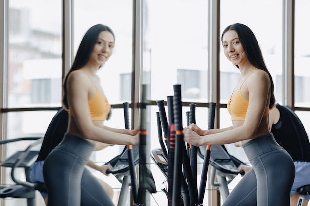 Young attractive girl at gym on exercise bike, fitness and yoga
