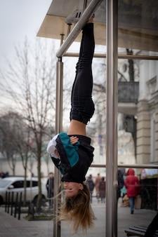 Молодая привлекательная девушка висит ногами вверх ногами на улице.