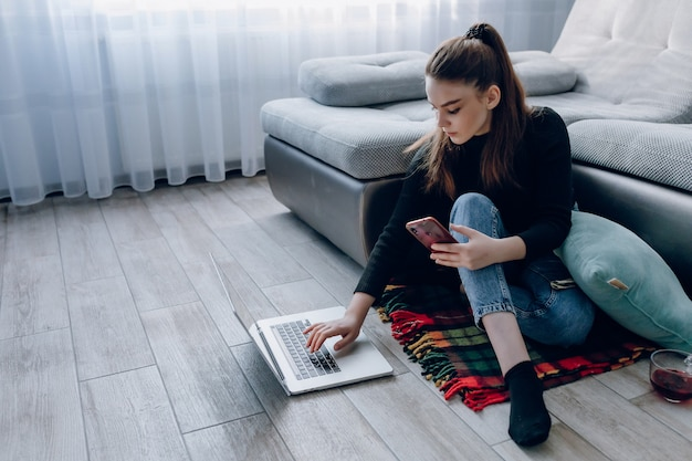 Young attractive girl at home working with a laptop and talking on the phone. comfort and coziness while at home. home office and work from home. remote online employment.