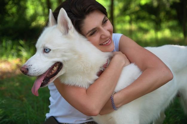 Молодая привлекательная девушка обнимает ее собаку