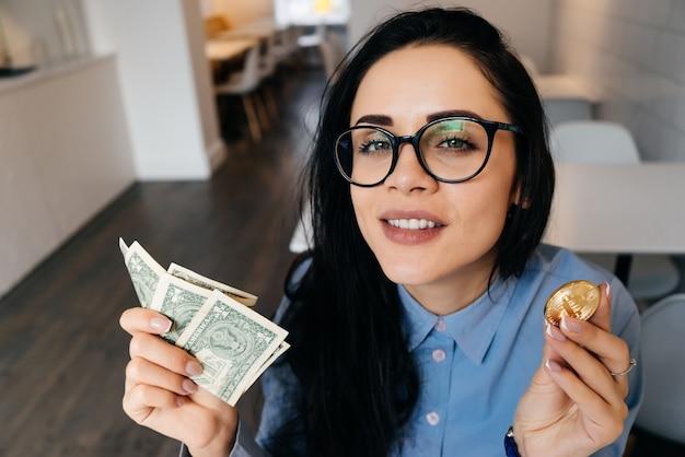 Молодая привлекательная девушка в синей рубашке и очках держит в руках доллары и золотые биткойны