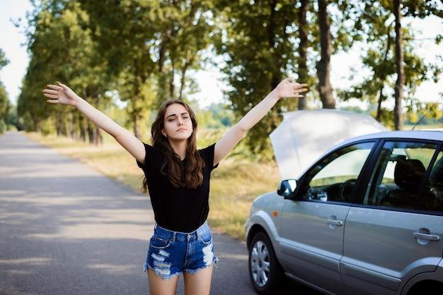Молодая привлекательная девушка в отчаянии останавливает прохожего на машине