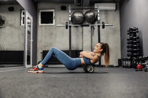 스포츠웨어에 젊은 매력적인 여자는 스포츠 롤러 마사지로 그녀의 등 근육을 마사지