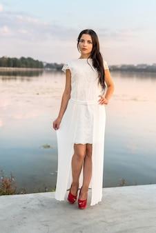 屋外でポーズをとる夏のドレスの若い魅力的な女の子