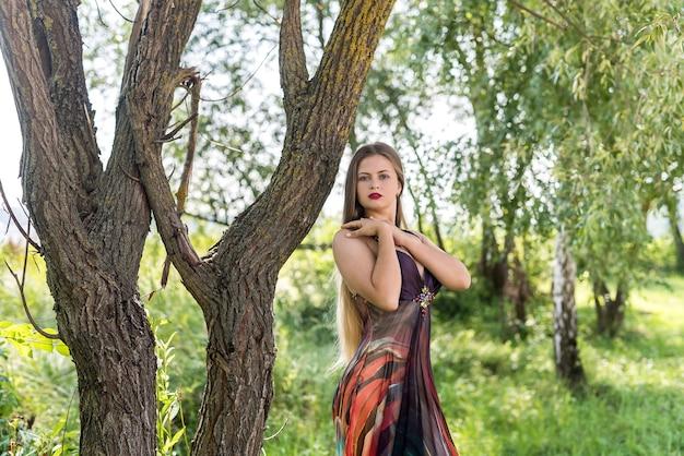 Молодая привлекательная девушка в летнем платье позирует на открытом воздухе