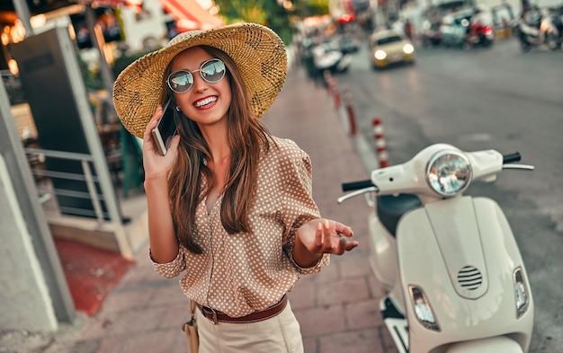 Молодая привлекательная девушка в солнечных очках и соломенной шляпе разговаривает по телефону, стоя возле скутера на городской улице. путешествия, концепция туризма.