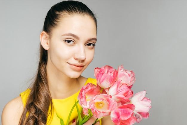 노란 드레스를 입은 젊은 매력적인 소녀는 봄 날씨에 분홍색 꽃의 큰 꽃다발을 들고 있습니다