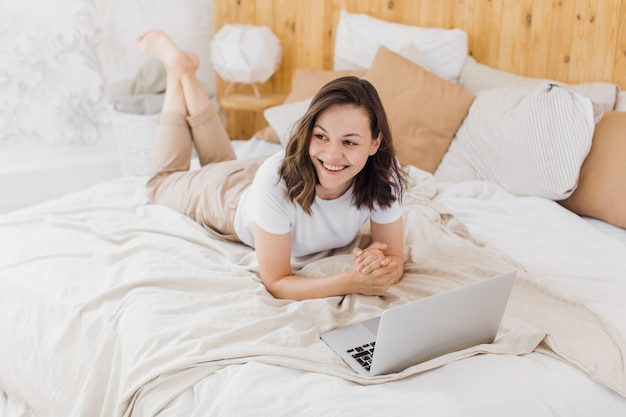 A young attractive girl is lying in bed and checking social networks modern bright apartment
