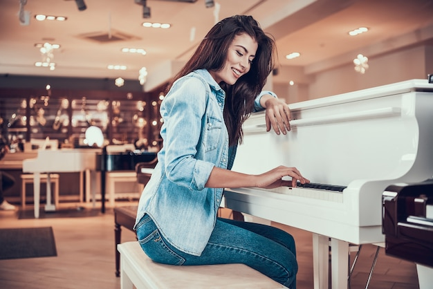 Young attractive girl is playing piano in music store.
