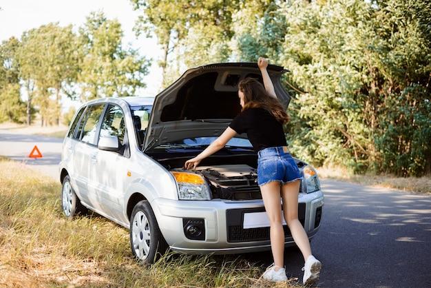 Молодая привлекательная девушка возле открытого капота автомобиля на обочине пытается решить проблему