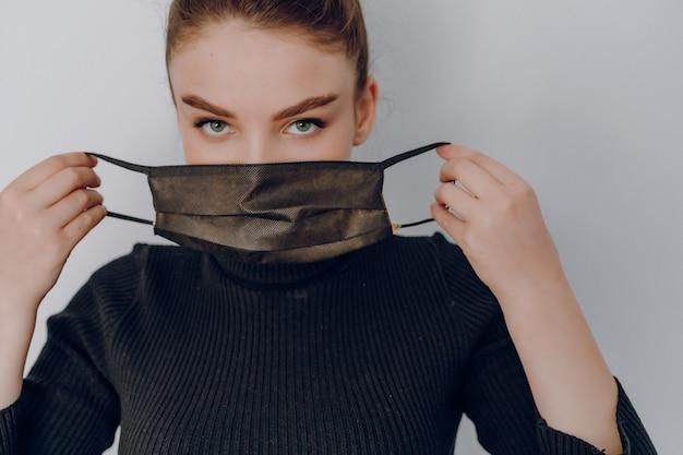 가벼운 벽에 젊은 매력적인 여자 의료 마스크를 착용. 개인 보호 사용. 사람의 전염병 및 오염 방지 보호.