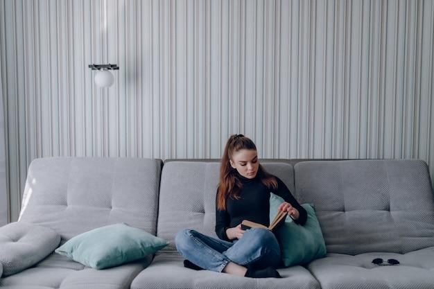 ソファの上の魅力的な少女は紙の本を読みます。精神発達。自宅での時間の有効活用。家の快適さ。