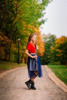 Молодая привлекательная девушка играет на кларнете, черное дерево в осеннем парке
