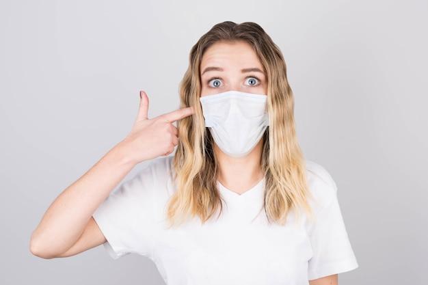 젊은 매력적인 여자는 그녀의 얼굴에 의료 보호 마스크에 그녀의 손가락을 가리 킵니다.