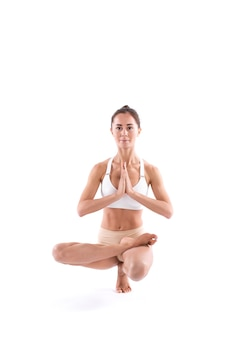 Young attractive girl practicing yoga isolated on white background. control balance exercise, studio full length.