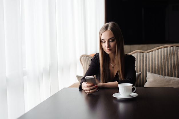 Young attractive girl sitting alone near big window