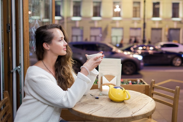 Young attractive girl sitting in the evening in a cafe.