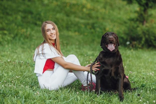 彼女の親友と草の上に座っている若い魅力的な女の子