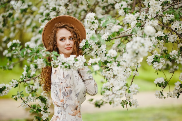 Young attractive girl stands among white blooming trees at the park. a woman wearing brown hat and white dress enjoys spring season. fresh garden and change of seasons concept.