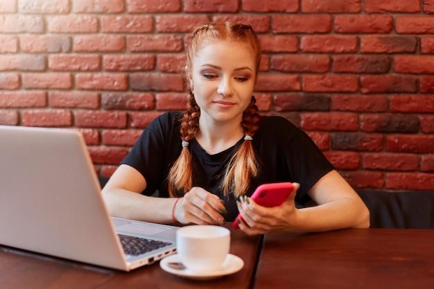 Молодая привлекательная девушка серфинг в интернете через мобильный телефон и улыбка, сидя в одиночестве в кафе во время работы на ноутбуке