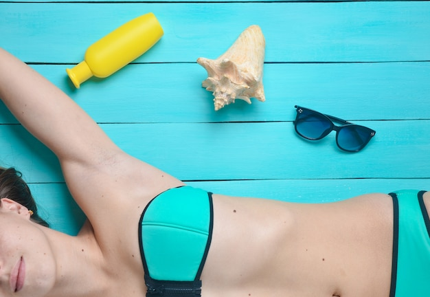 A young attractive girl in a swimsuit enjoys relaxing and sunbathing on a blue wooden surface. accessories for the resort rest on the beach: sunblock, sunglasses, shell. top view.